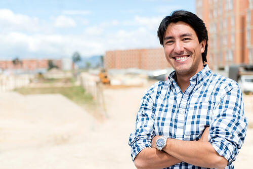 Man at a construction site looking very happy